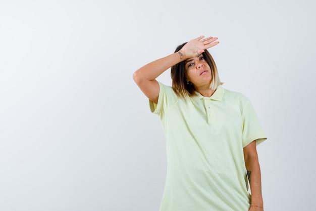 머리 위로 손으로 멀리보고 잠겨있는, 전면보기를 찾고 t- 셔츠에 어린 소녀.