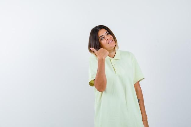 엄지 손가락으로 제쳐두고 가리키는 유쾌한, 전면보기 T- 셔츠에 어린 소녀. 무료 사진