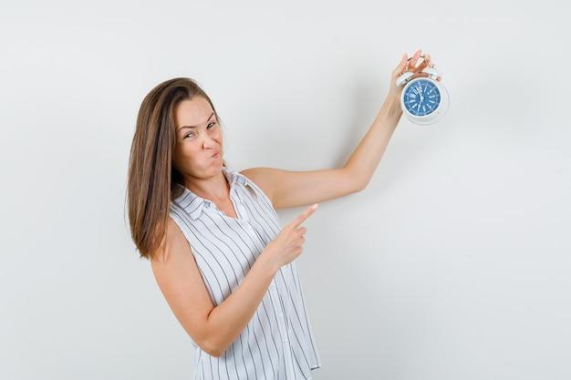 目覚まし時計を指して、疑わしい、正面図を探しているtシャツの少女。