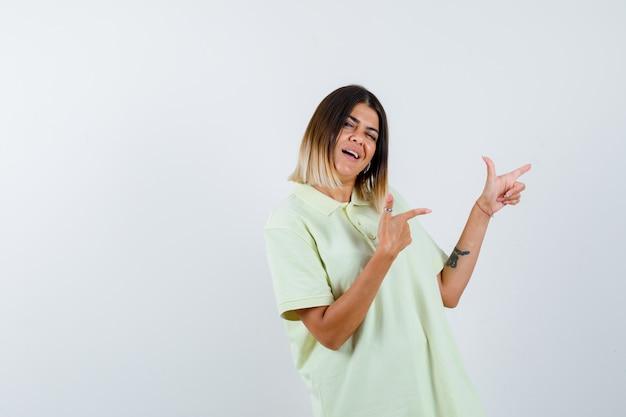 人差し指で右を指し、陽気な、正面図を見てtシャツの少女。