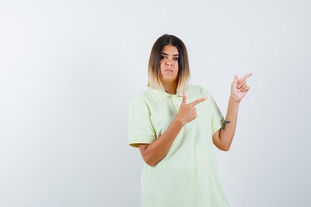 人差し指で右を指し、真剣に見えるtシャツの少女、正面図。