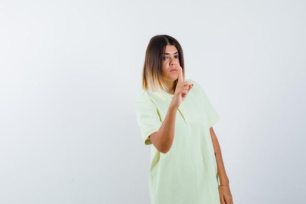T- 셔츠 표시에 어린 소녀 분 제스처에 보류 하 고 자신감, 전면보기를 찾고.