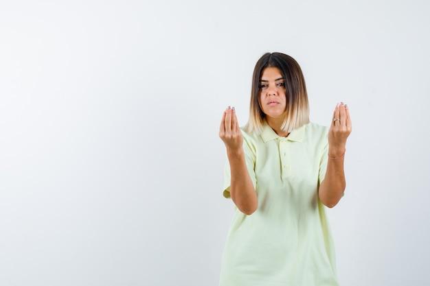 イタリアのジェスチャーを示し、真剣に見えるtシャツの少女、正面図。