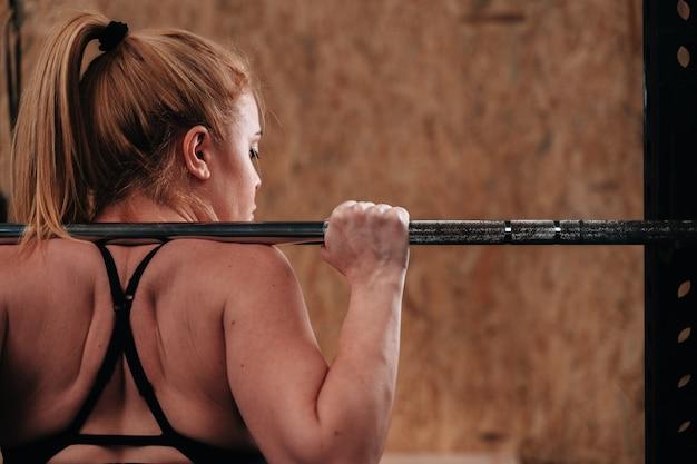 Молодая девушка на фоне тренажерного зала crossfit, делая тренировку мертвым весом.