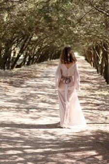 Молодая девушка в лесу в длинном винтажном платье, стоя спиной.