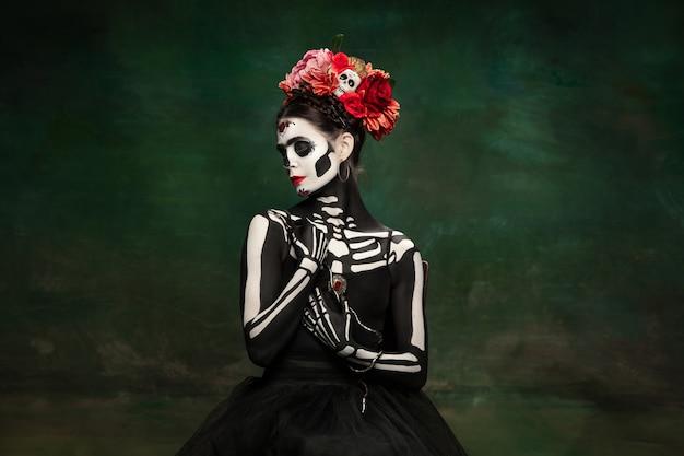 밝은 화장을 한 산타 무에르테, 성자 죽음 또는 설탕 두개골의 이미지에 있는 어린 소녀.