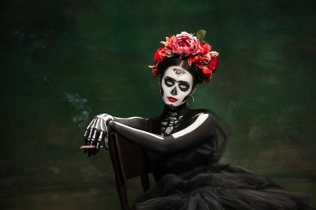 明るい化粧の肖像画とサンタムエルテ聖人の死または砂糖の頭蓋骨をイメージした少女