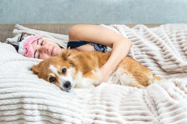그녀의 강아지와 함께 침대에서 아침에 어린 소녀. 집에서 개념 동물입니다.