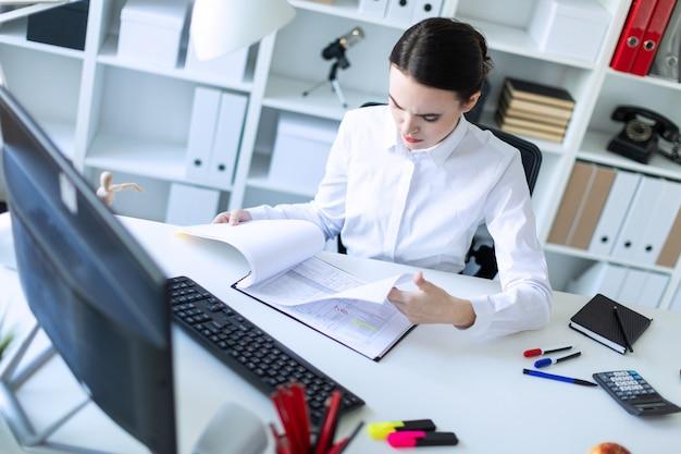 コンピューターでドキュメントを扱うオフィスの若い女の子。