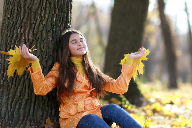 木の上のオレンジの葉と秋の時間の間に公園で若い女の子