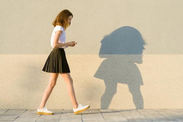 プロファイルの少女、携帯電話で灰色の壁に沿って歩く