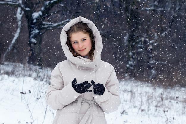 降雪時の冬の森の少女。冬の森の若い幸せな女の子の肖像画