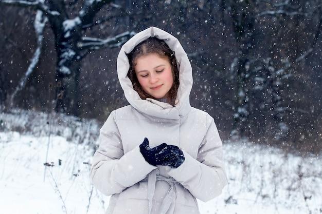 Молодая девушка в зимнем лесу во время снегопада. портрет молодой счастливой девушки в зимнем лесу