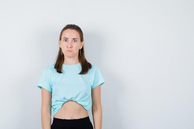 ターコイズブルーのtシャツを着た少女、カメラを見ているズボン、膨らんだ目とショックを受けた顔、正面図。