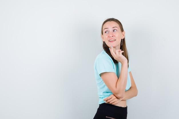 ターコイズ色のtシャツを着た少女、あごに指を置いたズボン、横向きに立って思慮深く見える。