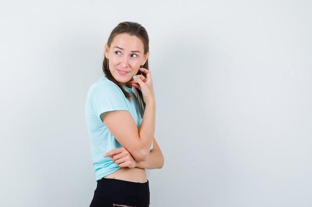 ターコイズ色のtシャツを着た少女、顔の近くに手があり、思慮深く見えるパンツ。