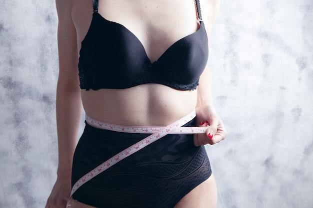 下着姿の少女が腹部の胴回りを測る