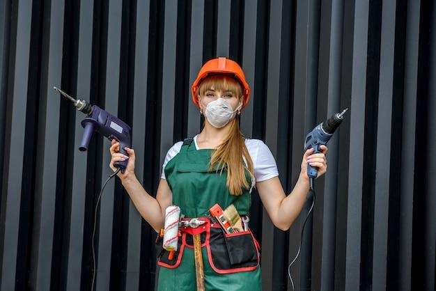 Молодая девушка в форме и шлеме делает ремонт с помощью дрели.