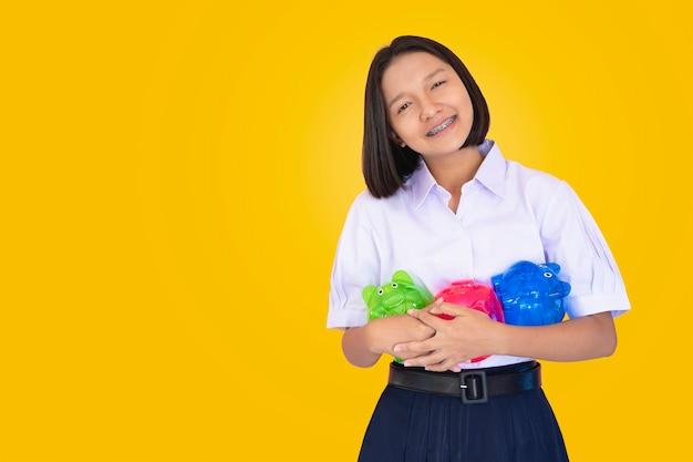 制服の学生の若い女の子は、背景が黄色の3つの貯金箱を保持しています。