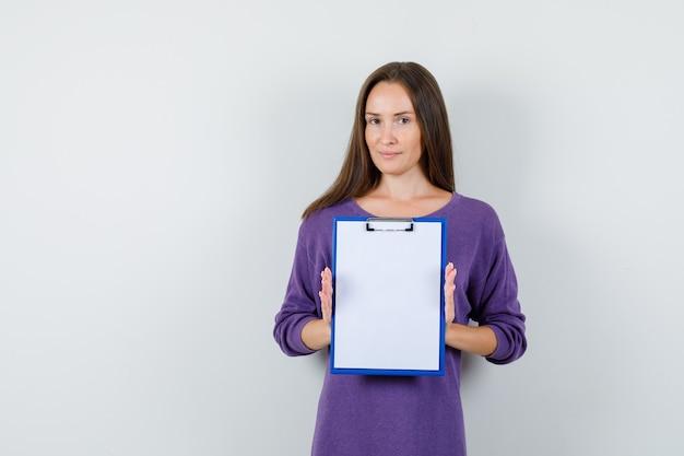 Молодая девушка в фиолетовой рубашке с буфером обмена и улыбается, вид спереди.