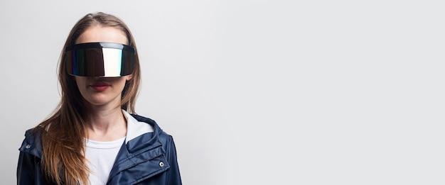 Молодая девушка в очках виртуальной реальности в синей куртке на светлом фоне. баннер.