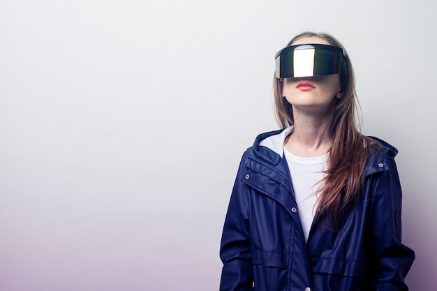 Молодая девушка в очках виртуальной реальности в синей куртке на светлом фоне.
