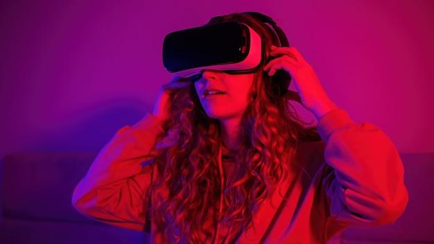 部屋に青と赤のイルミネーションとバーチャルリアリティメガネの少女。自宅でのエンターテインメント