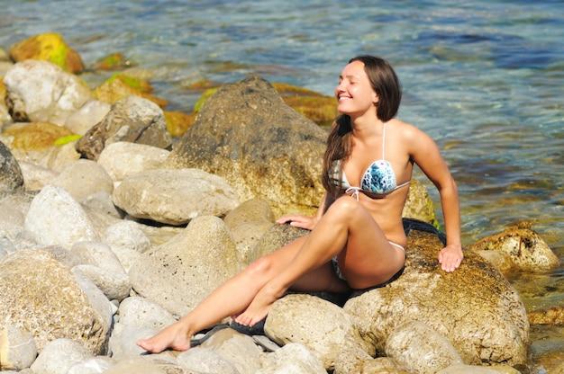 눈을 감고 포즈를 취하는 흰색과 파란색 수영복에 어린 소녀가 바다 근처에 큰 돌맹이에 앉아