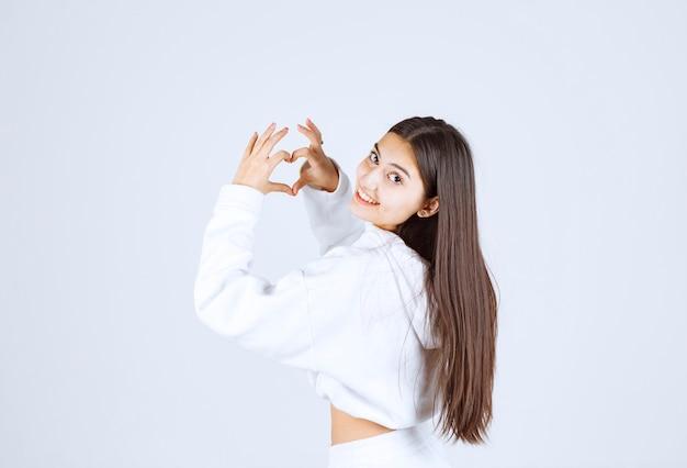 Молодая девушка в белой толстовке с капюшоном, показывая сердце двумя руками.