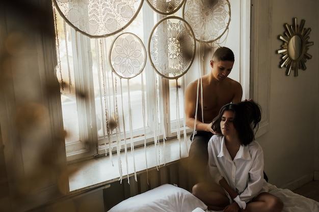 白い男性のシャツを着た若い女の子と窓の近くの寝室に座っている裸の胴体を持つ男と男は女の子の髪で遊ぶ。