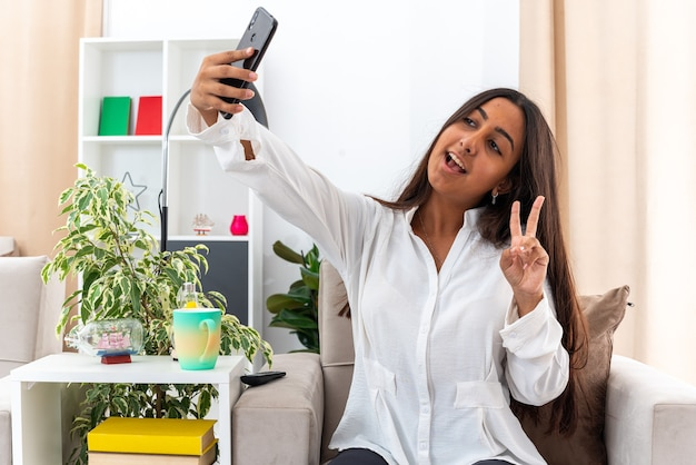 Молодая девушка в белой рубашке и черных штанах делает селфи с помощью смартфона, счастливая и веселая, показывая v-знак, сидя на стуле в светлой гостиной