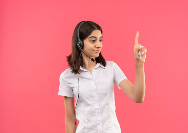 흰색 셔츠와 헤드폰에 어린 소녀, 분홍색 벽 위에 서 검지 손가락을 옆으로 보여주는 찾고