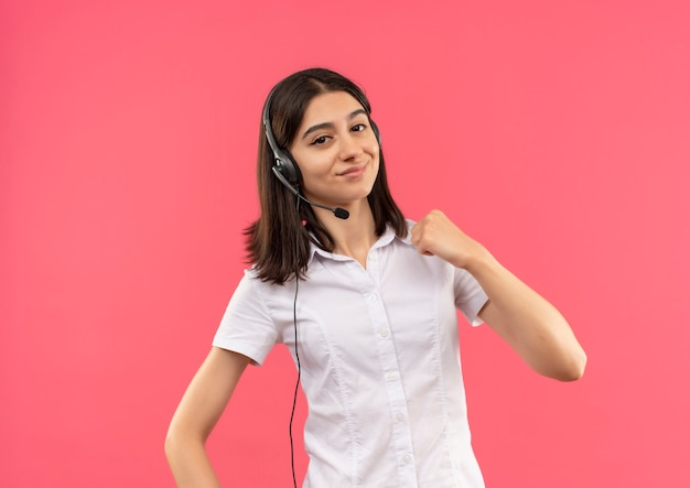 白いシャツとヘッドフォンで若い女の子、正面を見て笑顔の握りこぶし、ピンクの壁の上に立っている勝者の概念