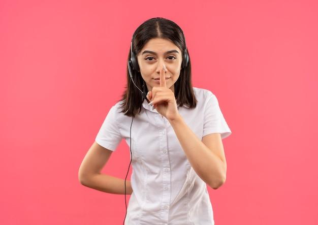 ピンクの壁の上に立っている唇に指で沈黙のジェスチャーをする白いシャツとヘッドフォンの少女