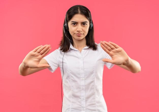 Молодая девушка в белой рубашке и наушниках делает знак остановки с руками, смотрящими вперед, с серьезным лицом, стоящим над розовой стеной