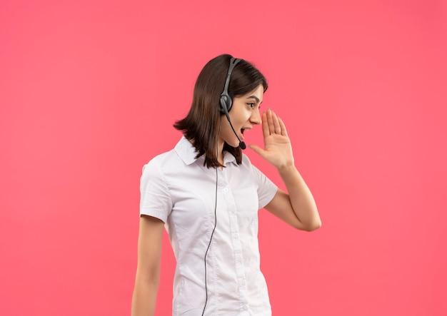 Молодая девушка в белой рубашке и наушниках, кричит или зовет кого-то рукой у рта, стоящего над розовой стеной