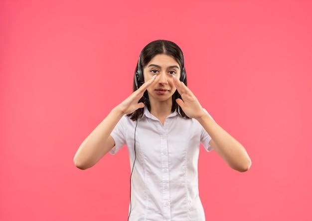 Молодая девушка в белой рубашке и наушниках, кричит или зовет кого-то руками возле рта, стоя над розовой стеной