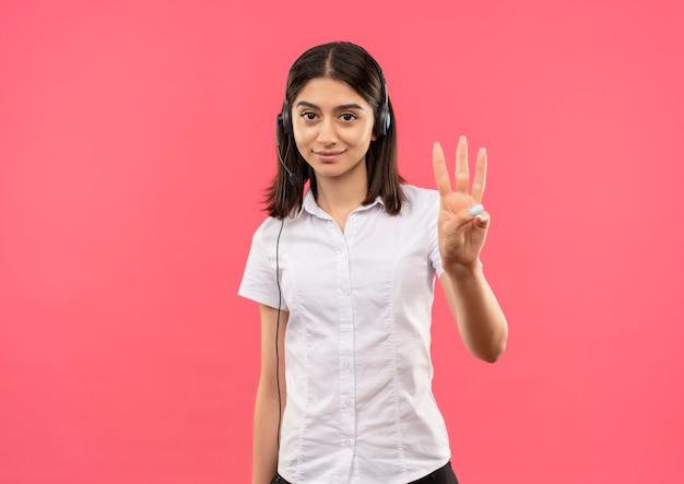 흰 셔츠와 헤드폰에 어린 소녀, 분홍색 벽 위에 서있는 미소 3 번까지 손가락으로 가리키는