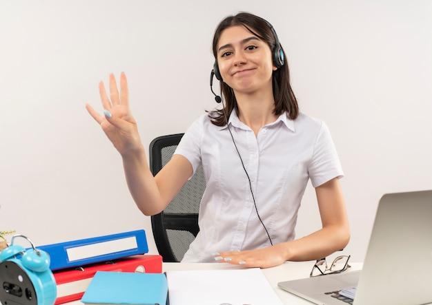 흰 셔츠와 헤드폰에 어린 소녀, 흰 벽 위에 폴더와 노트북 테이블에 앉아 웃고 손가락으로 세 번째를 보여주는