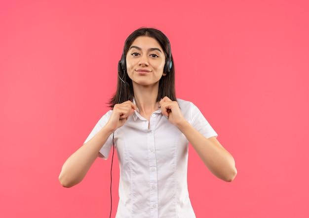 흰색 셔츠와 헤드폰에 어린 소녀, 분홍색 벽 위에 자신감 서 찾고 그녀의 칼라를 만지고
