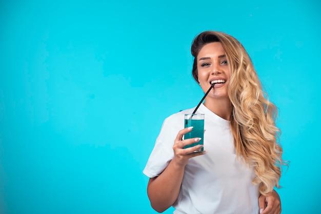 Молодая девушка в белой рубашке, пить синий коктейль.