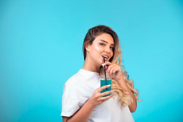 Молодая девушка в белой рубашке пьет синий коктейль