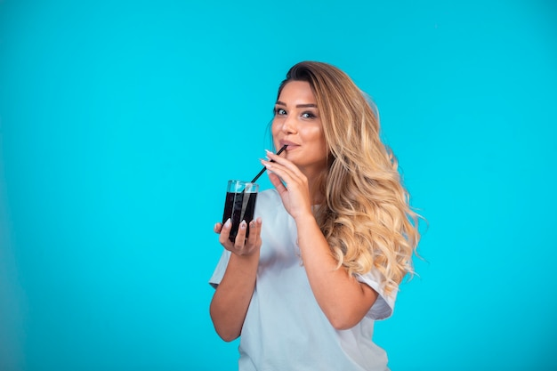 Молодая девушка в белой рубашке держит стакан черного коктейля и проверяет вкус