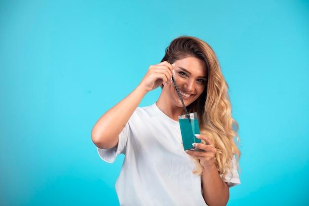 Молодая девушка в белой рубашке держит стакан синего коктейля и чувствует себя позитивно