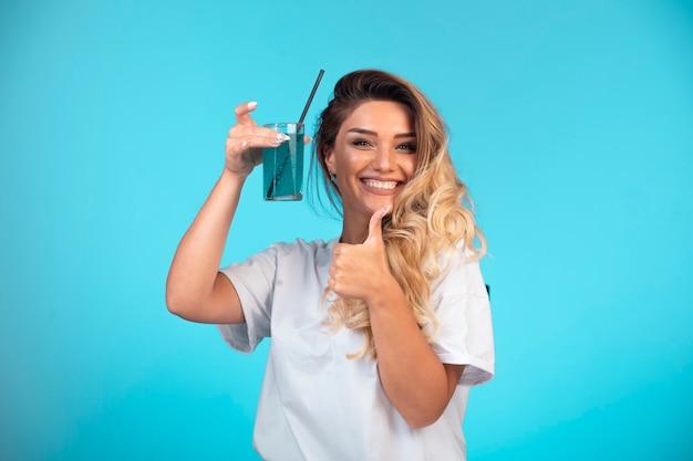 青いカクテルのグラスを保持している白いシャツの少女。