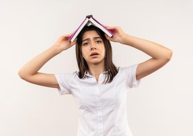 Молодая девушка в белой рубашке держит открытую книгу над головой, выглядит смущенной, стоя над белой стеной
