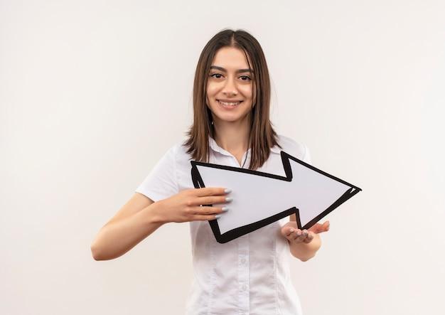 흰색 벽 위에 서 웃 고 전면을 찾고 흰색 화살표를 들고 흰 셔츠에 어린 소녀