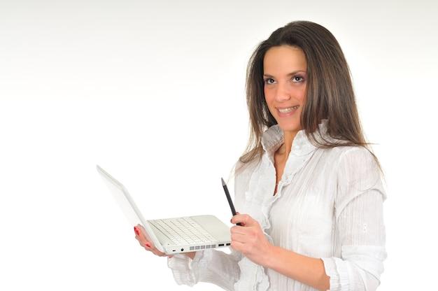Молодая девушка в белой рубашке держит в руках белый ноутбук. изолированные на белой стене