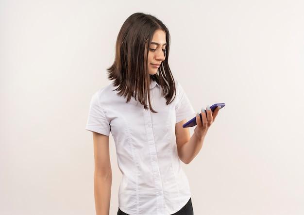 白い壁の上に立っている顔に笑顔で彼女の携帯電話の画面を見ている白いシャツの少女