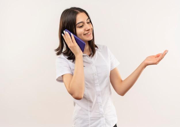 Молодая девушка в белой рубашке разговаривает по мобильному телефону с улыбкой на лице, стоящей над белой стеной